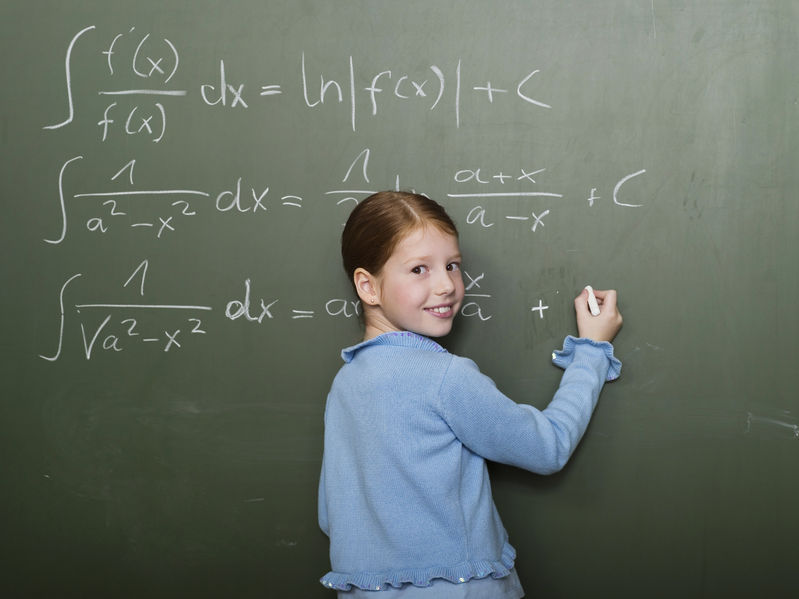 29829112 - girl standing in front of blackboard, solving arithmetic problem